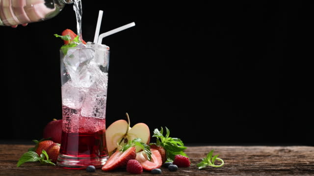 mixed fruit juice with syrup and soda surrounded by fruits - healthy green juice video stock e b–roll