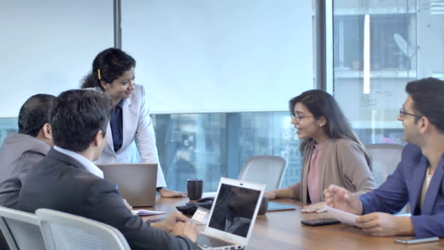 a mixed gender business group talking in a office boardroom - india video stock e b–roll