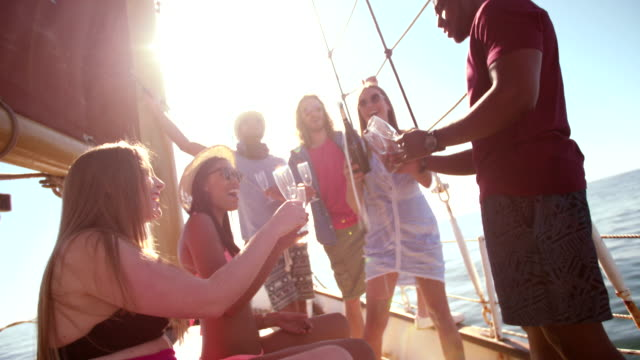 Mixed group of friends on yacht drinking champagne with sunflare Mixed race friends having a party and  drinking champagne on a yacht with summer sunflare yacht stock videos & royalty-free footage
