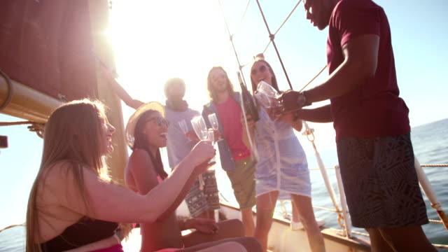 vídeos y material grabado en eventos de stock de mezclan grupo de amigos en alquiler de barcos bebiendo champán con sunflare - yacht