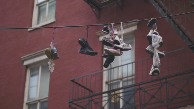 Mixed Old Shoes Hanging on a Wire A mixed group of old used shoes are hanging on a string in New York city. Handheld shot in 4K resolution. poverty stock videos & royalty-free footage