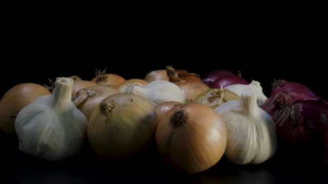 mixed organic onions rotating against black background - aglio cipolla isolated video stock e b–roll