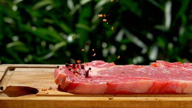 vídeos de stock e filmes b-roll de mixed pepper and spices are falling on a raw meat - beef angus