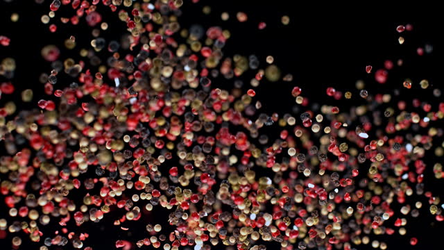 SLO MO LD Mixed peppercorns flying into the air