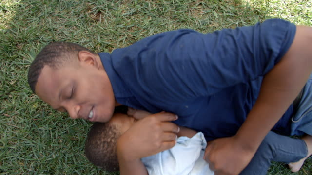 mixed race black father play fighting with young son in park - wrestling stock videos and b-roll footage