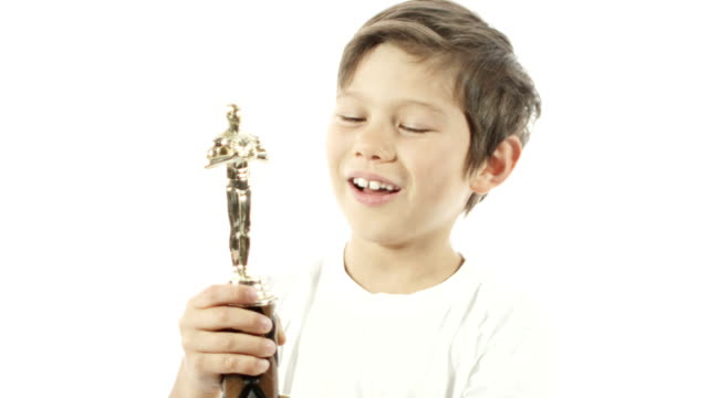 A mixed race boy celebrates with his trophy in slow motion. video