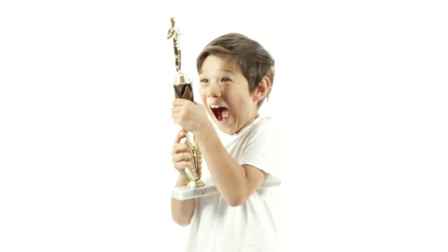 a mixed race boy celebrates with his trophy in slow motion. - zachęta filmów i materiałów b-roll