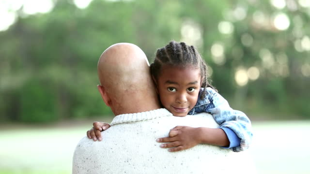 Mixed race boy in father's arms, looking over shoulder
