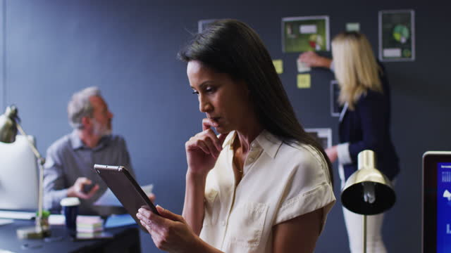 Mixed race businesswoman using digital tablet in office with colleagues discussing behind