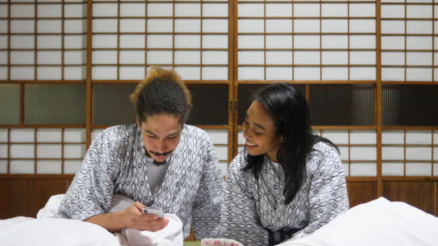 Mixed Race Couple Looking at a Phone in a Japanese Futon Bed