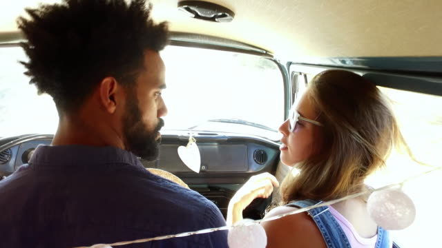 Mixed race couple on sitting in the front of camper van Mixed race couple on sitting in the front of camper van rv interior stock videos & royalty-free footage