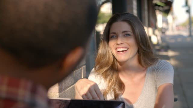 Mixed race couple relaxing at a table outside a coffee shop video