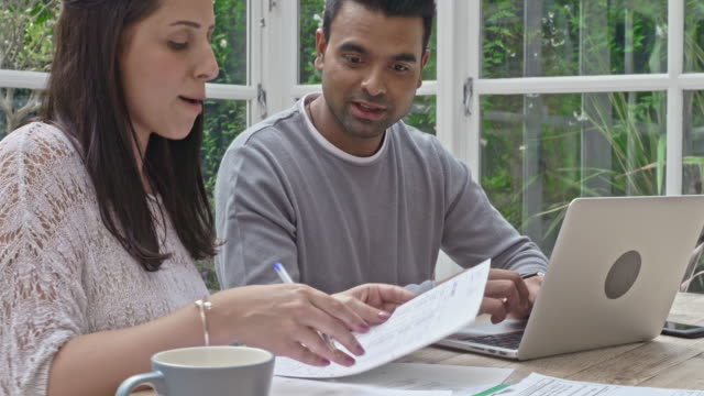 Mixed race couple working on the home finances at home video