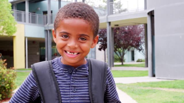 mixed race elementary schoolboy smiling to camera, outdoors - solo un bambino maschio video stock e b–roll