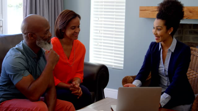 Mixed race female real estate agent discussing over property with mature couple on laptop at home 4k