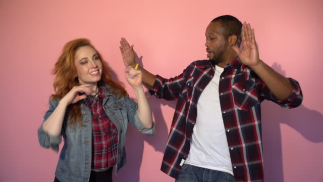 Mixed Race Hipster Couple Dancing in front of Pink Background African American male and a red headed caucasian female dance in front of a pink background looking happy and getting their groove on. background color stock videos & royalty-free footage