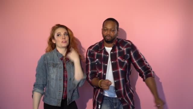 Mixed Race Hipster Couple Dancing in front of Pink Background video