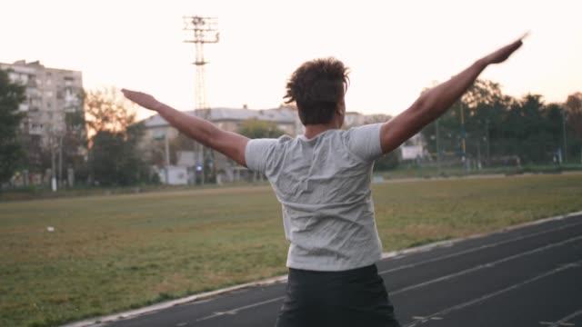 vídeos de stock e filmes b-roll de mixed race man athlete warming up doing jumping jacks before running or work out - campeão desportivo
