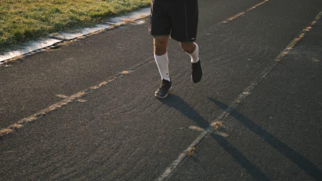 vídeos de stock e filmes b-roll de mixed race man athlete warming up legs before running or work out - campeão desportivo