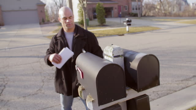 Mixed race man collects his mail in Mid West suburb video