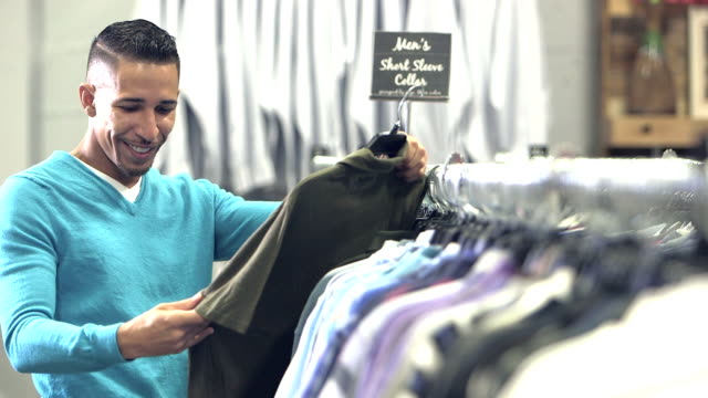 Mixed race man shopping in clothing store video