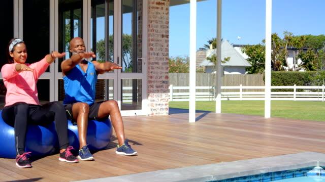 vídeos de stock e filmes b-roll de mixed race mature couple exercising together on exercise ball  at backyard on a sunny day 4k - 55 59 anos