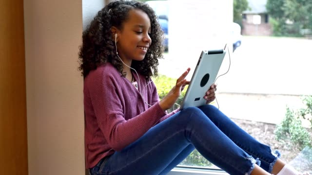 Mixed race middle schoolgirl uses digital tablet at school