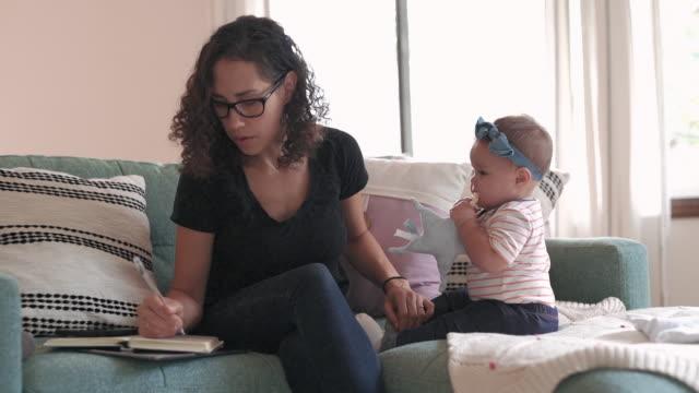 blandad ras mamma arbetar hemifrån med sitt barn - working from home bildbanksvideor och videomaterial från bakom kulisserna