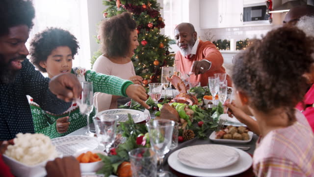 mixed race, multi generation family sitting at their christmas dinner table serving themselves food and talking together, selective focus - cena natale video stock e b–roll