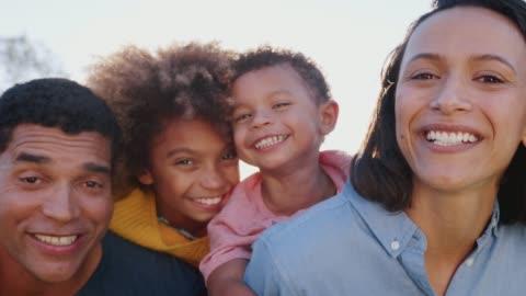 genitori di razza mista che fanno il piggybacking dei loro figli in giardino, guardando la macchina fotografica e ridendo, da vicino - etnia latino americana video stock e b–roll