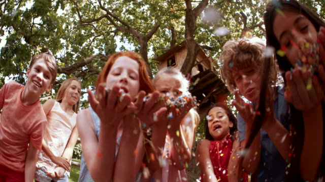 mixed race person of children blowing handfuls of colorful confetti video