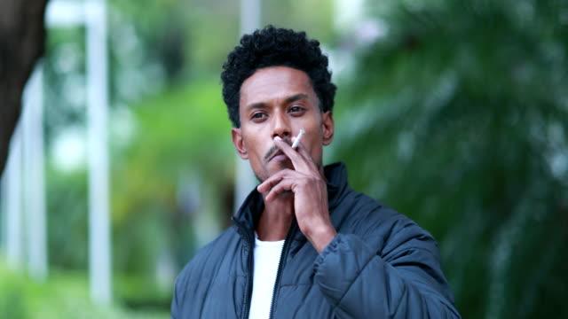 karışık ırk portre adam sigara tütün açık havada, sağlıksız alışkanlığı sigara - nikotin stok videoları ve detay görüntü çekimi