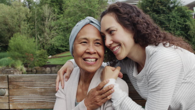 Mixed race senior woman sitting with her adult daughter outdoors An adult daughter embraces her senior mother with cancer. They're outside on a bench and both are smiling and happy to be together. gratitude stock videos & royalty-free footage