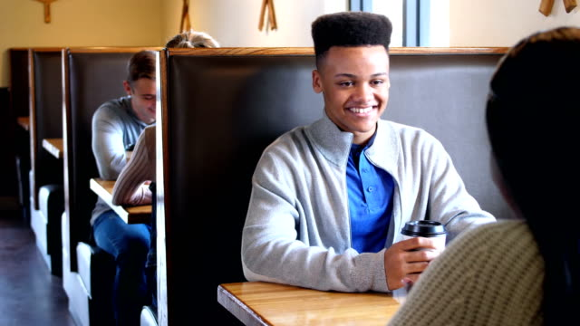 Mixed race teenage boy in coffee shop with friend