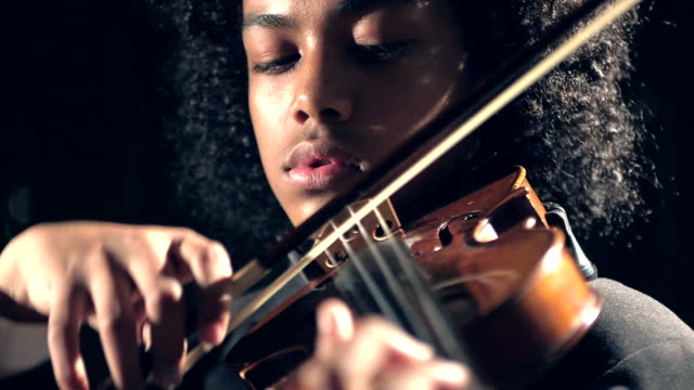 Mixed race teenage boy playing violin A mixed race African-American, Hispanic and Asian 16 year old boy playing the violin in a concert performance. He is wearing a tuxedo. classical concert stock videos & royalty-free footage