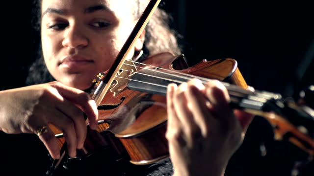 Mixed race teenage girl playing violin video
