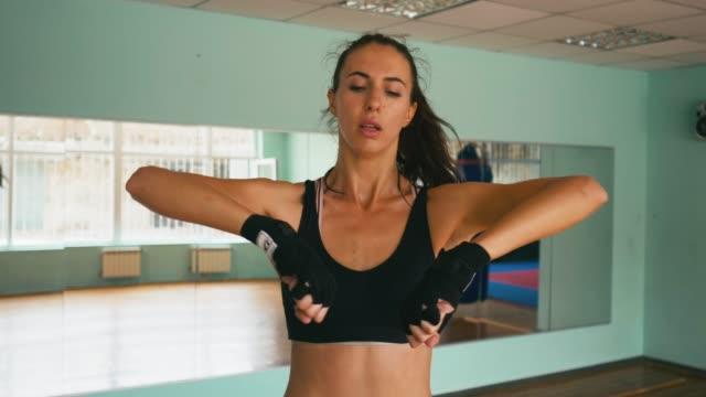 vídeos de stock e filmes b-roll de mixed race woman boxer warms up muscles before the fight. close up slow motion shot - campeão desportivo