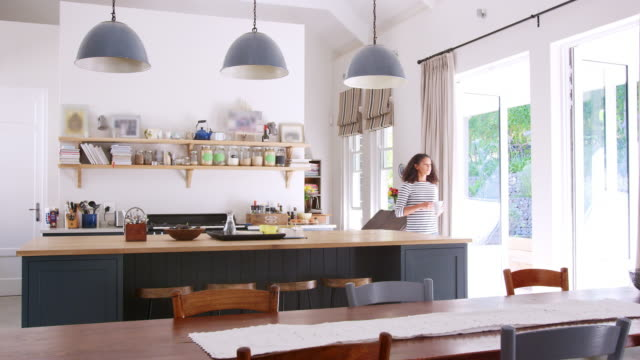 Mixed race woman drinking coffee in open plan kitchen