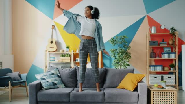 vídeos de stock, filmes e b-roll de mulher mestiça em fones de ouvido dançando no sofá em apartamento se divertindo - adolescência