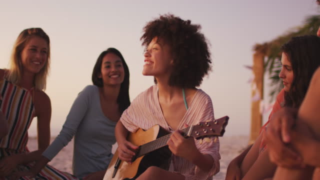 Mixed race woman playing guitar for her friends on the beach