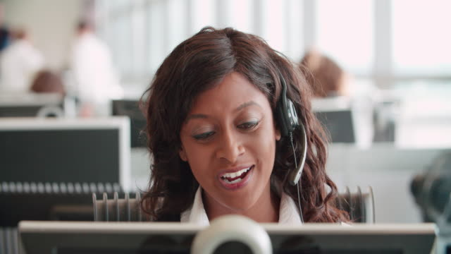 Mixed race woman working in a call centre using a headset Mixed race woman working in a call centre using a headset mixed race person stock videos & royalty-free footage