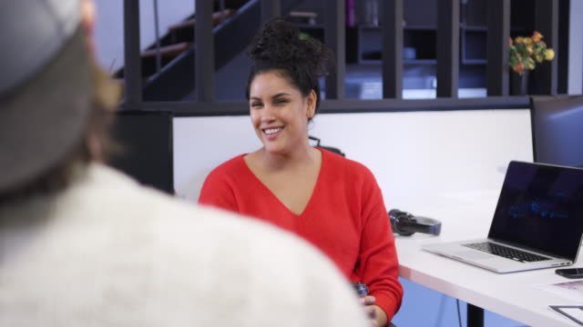 Mixed race woman working in creative office Front view of a happy mixed race woman working in a creative office, sitting at a desk, smiling and talking to her male colleague, slow motion employee engagement stock videos & royalty-free footage