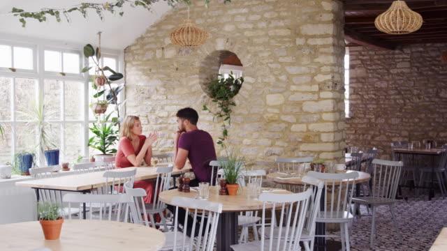 手を繋いでいると空のレストランで話のテーブルに座って混血若い大人カップル - 石垣点の映像素材/bロール
