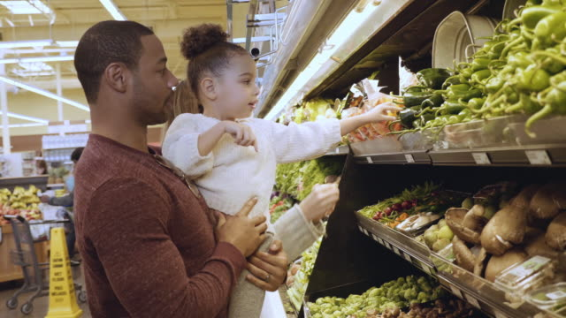 Mixed Race Young Family Shopping for Vegetables A mixed race family with a young daughter shop in the produce section of a grocery store consumerism stock videos & royalty-free footage