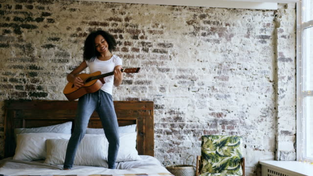 Mixed race young funny girl singing and playing acoustic guitar while have fun dancing on bed at home video