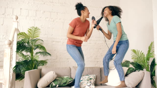mixed race young funny girls dance singing with hairdryer and comb jumping on sofa. sisters having fun leisure in living room at home concept - śpiewać filmów i materiałów b-roll
