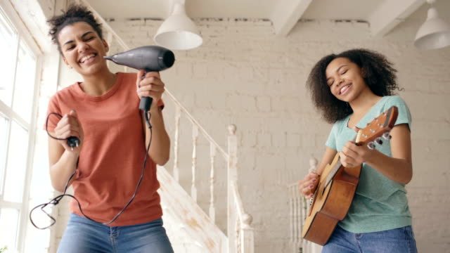 Mixed race young funny girls dance singing with hairdryer and playing acoustic guitar on a bed. Sisters having fun leisure in bedroom at home video