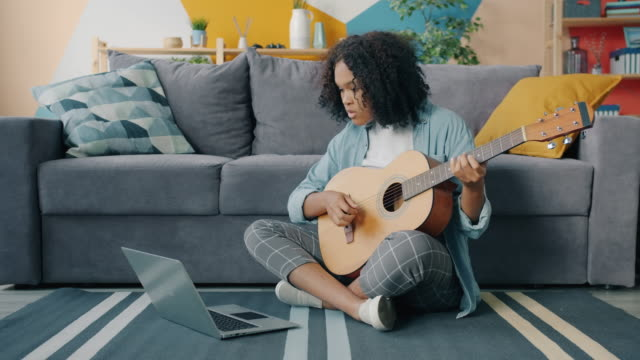 Mixed race young woman is learning to play the guitar using laptop at home