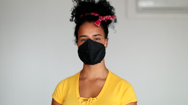 vídeos de stock e filmes b-roll de mixed race young woman puts face mask prevention against virus outbreak - afro latino mask