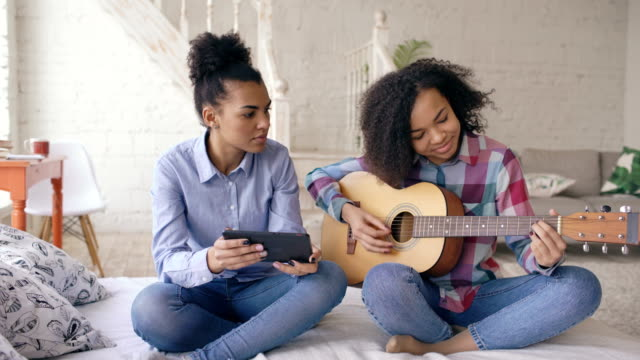 mixed race young woman with tablet computer sitting on bed teaching her teenage sister to play acoustic guitar at home - praticare video stock e b–roll